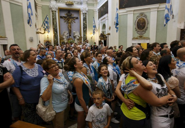 """People sing in the church as Onda (sea wave) parish's horse """"Osama Bin"""" is blessed in the church before the Palio horse race in Siena July 2, 2015. (Photo by Max Rossi/Reuters)"""