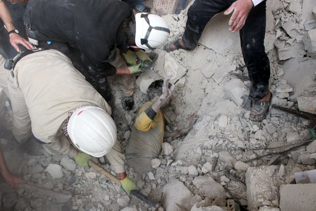 Emergency responders rescue a man buried under rubble after a building collapsed following a reported barrel-bomb attack on the northern Syrian city of Aleppo, on April 25, 2014. Syria's Aleppo has been hit by a power cut for seven consecutive days, the Syrian Observatory for Human Rights group said, the day after some 50 civilians were killed in air raids there. (Photo by Baraa Al-Halabi/AFP Photo)