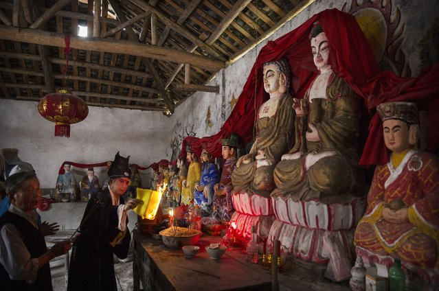 Sichuan Opera performer Wu Dezhi, 51 years, of the Jinyuan Opera Company performs a prayer ritual in front of statues of the Buddha before the group's performance for villagers at the Dongyue Temple on May 2, 2016 in Cangshan, Sichuan province, China. (Photo by Kevin Frayer/Getty Images)