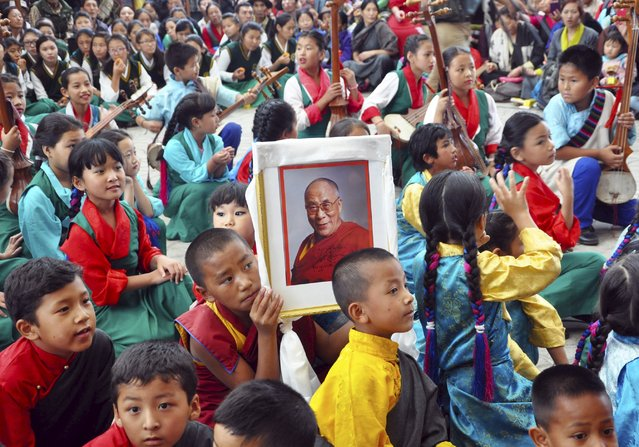 A young Tibetan monk holds a portrait of their spiritual leader, the Dalai Lama, during celebrations marking his 80th birthday anniversary in the northern hill town of Dharamsala, India July 6, 2015. (Photo by Reuters/Stringer)