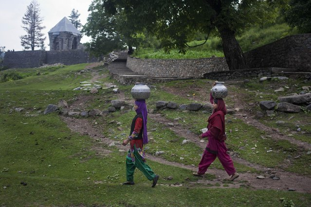 Kashmiri village women walk carrying vessels filled with drinking water in Wangath, Some 48 kilometers (30 miles) northwest of Srinagar, Indian controlled Kashmir, Tuesday, July 7, 2015. Most of the villagers living around Wangath have to walk long distance to fetch drinking water. (Photo by Dar Yasin/AP Photo)
