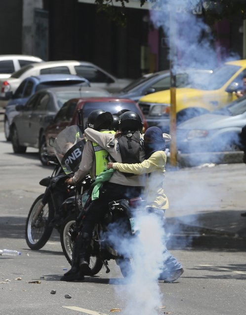 A demonstrator, right, grabs a Bolivarian National Police officer tearing him off the back of a motorcycle during a protest in Caracas, Venezuela, Monday, April 10, 2017. The officer was attacked by demonstrators, his helmet was torn off but was able to brake off and run to safety. The motorcycle was eventually recovered too. Thousands of people in Venezuela's capital are protesting against the government of President Nicolas Maduro, demanding new elections and vowing to stay in the streets during the usually quiet Easter Week. (Photo by Fernando Llano/AP Photo)