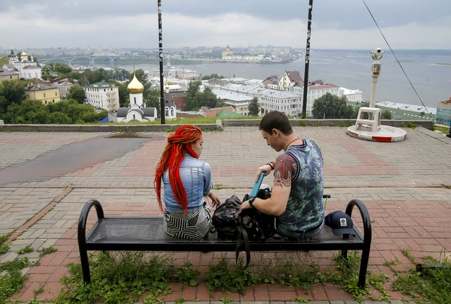 A couple sit facing the backdrop of the Volga river in the town of Nizhny Novgorod, Russia, July 10, 2015. (Photo by Maxim Shemetov/Reuters)