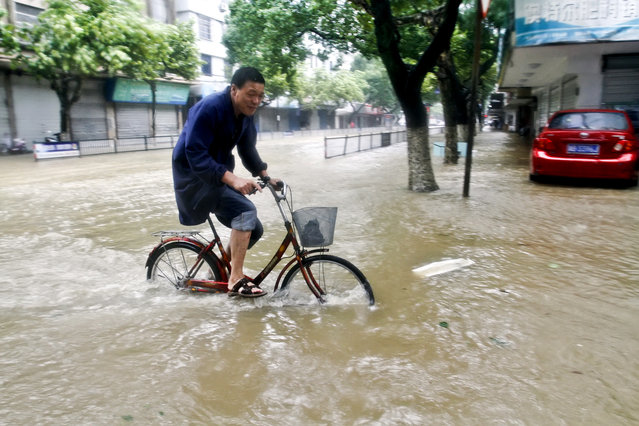 In this photo provided by China's Xinhua News Agency, a resident rides a bicycle on a road submerged by water in Xiangshan county,  east China's Zhejiang Province, Saturday, July 11, 2015. Typhoon Chan-hom hit the Chinese coast south of Shanghai on Saturday with winds gusting up to 200 kph (125 mph) after nearly 1 million people were evacuated and hundreds of airline flights canceled, state television reported. (Photo by He Yousong/Xinhua News Agency via AP Photo)