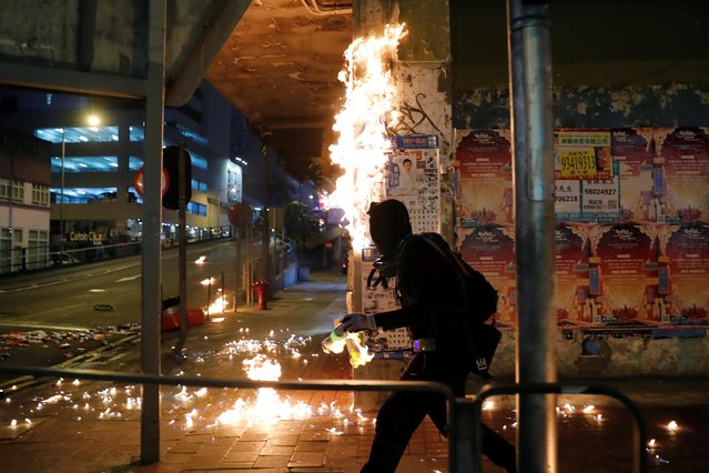 Anti-government protester throws molotov cocktail as they retreat after a clash with riot police in Hong Kong, China on September 29, 2019. (Photo by Tyrone Siu/Reuters)