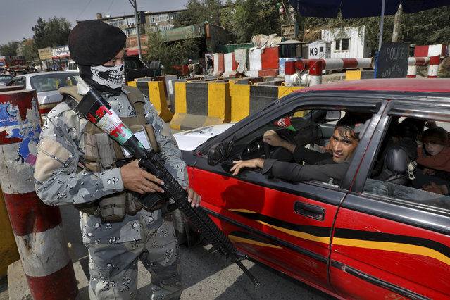 In this Wednesday, September 25, 2019 photo, a masked Afghan policeman stands guard at a checkpoint ahead of presidential elections scheduled for Sept. 28, in Kabul, Afghanistan. Afghans facing down Taliban threats are torn between fear, frustration and sense of duty as they decide whether to go to the polls Saturday to choose a new president. (Photo by Ebrahim Noroozi/AP Photo)
