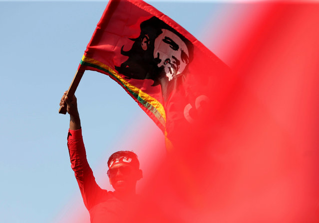 A man waves a flag with an image of Che Guevara at a march during the May Day or Labour Day rally organised by People's Liberation Front opposition party in Colombo, Sri Lanka. (Photo by Dinuka Liyanawatte/Reuters)