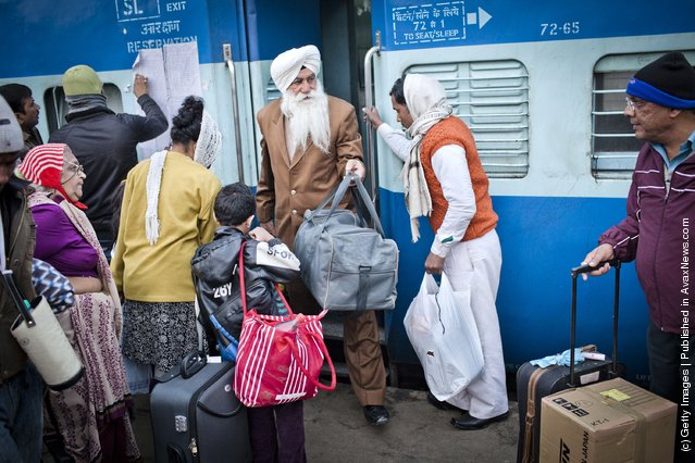 A man alights from a carriage, as others wait to board the Amritsar bound train at the  Nizamuddin Railway Station in New Delhi, India