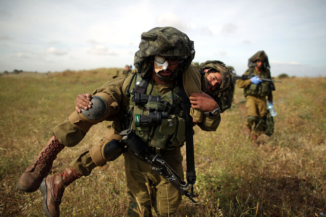 An Israeli soldier from the Netzach Yehuda brigade, the Israeli army battalion for Orthodox soldiers and Yeshiva students, carries a simulated casualty during the battalion ground maneuver exercise in the Golan Heights near the Israeli-Syrian border, May 19, 2014. (Photo by Abir Sultan/EPA)