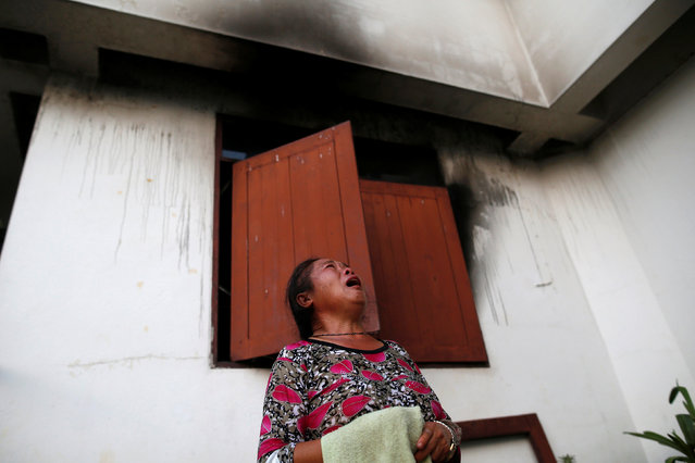 A woman cries in front of a burnt building at the Pitakkiat Wittaya School in the northern province of Chiang Rai, Thailand, May 23, 2016. (Photo by Athit Perawongmetha/Reuters)