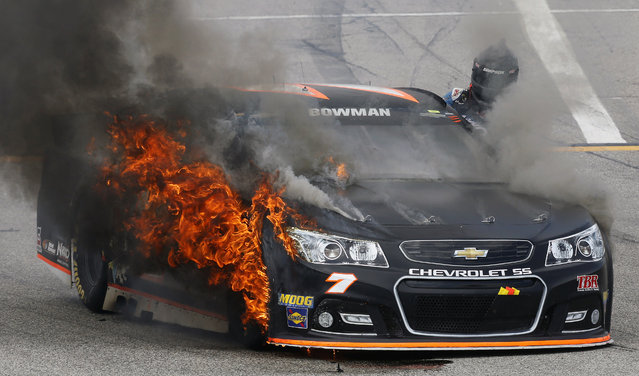 Alex Bowman climbs out of his burning car during the NASCAR Sprint Cup series auto race at New Hampshire Motor Speedway, Sunday, July 19, 2015, in Loudon, N.H. (Photo by Jim Cole/AP Photo)