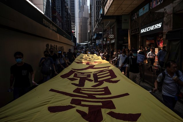 "People carry a banner during a pro-democracy ""flash mob"" rally at lunchtime in the Central district in Hong Kong on November 1, 2019. The semi-autonomous Chinese city has been upended by nearly five months of huge, often violent, pro-democracy demonstrations with little end in sight as Beijing and city leaders adopt a hardline approach. (Photo by Philip Fong/AFP Photo)"