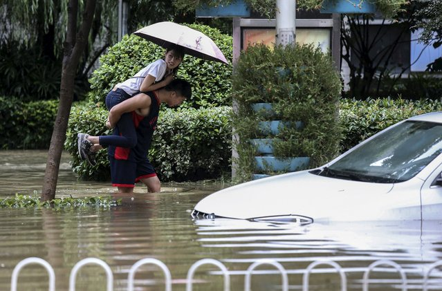 A man carries a woman on his back as he walks on a flooded street amid heavy rainfall in Wuhan, Hubei province, China, July 23, 2015. Severe downpours hit the city on Thursday, flooding streets and shutting down public transportations, local media reported. (Photo by Reuters/China Daily)