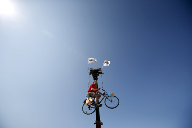A man rides a bicycle hanging from a crane during the 6th stage of the 102nd Tour de France cycling race from Abbeville to Le Havre, France, July 9, 2015. Photographing the Tour de France cycling race comes with highs and lows: the buzz from capturing just the right image, the tedium of long journeys, the painstaking set-up of equipment, the breath-taking scenery. (Photo by Eric Gaillard/Reuters)