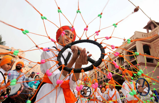 """A Sikh boy performs """"Gatkha"""", a traditional form of martial arts during a religious procession on the eve of the 550th birth anniversary of Guru Nanak Dev, the first Sikh Guru and founder of Sikh faith, in Amritsar, India, November 11, 2019. (Photo by Munish Sharma/Reuters)"""