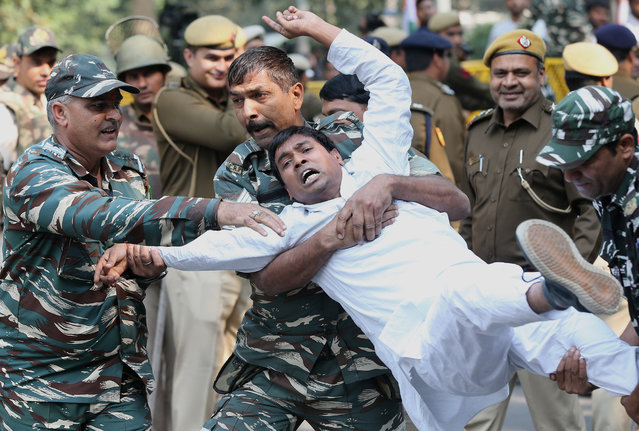 Security personnel detain an Indian Youth Congress (IYC) activist during a protest at Raisina road in New Delhi, India, 20 November 2019. Hundreds of IYC workers protested after Indian Government has downgraded the Gandhi family's security from Special Protection Group (SPG) security to Z-plus security cover of the Central Reserve Police Force (CRPF). Gandhi family has been under SPG cover since the assassination of the two former Indian prime ministers Indira Gandhi and Rajiv Gandhi who belonged to Indian Congress Party. (Photo by Harish Tyagi/EPA/EFE)