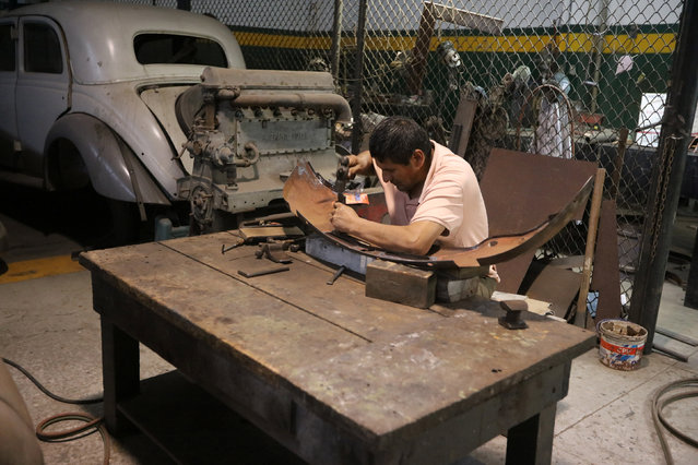 A car mechanic repairs a bumper at the Nicolini Collection Car Museum in Lima, Peru June 1, 2017. (Photo by Guadalupe Pardo/Reuters)