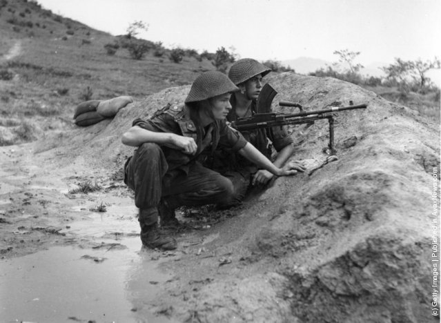 Two soldiers, guns at the ready, keep watch for enemy advance in Korea, 1950