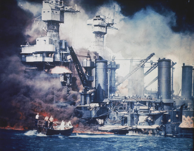 A small boat rescues a USS West Virginia crew member from the water after the Japanese bombing of Pearl Harbor, Hawaii on December 7, 1941 during World War II.  Two men can be seen on the superstructure, upper center.  The mast of the USS Tennessee is beyond the burning West Virginia. (Photo by AP Photo)