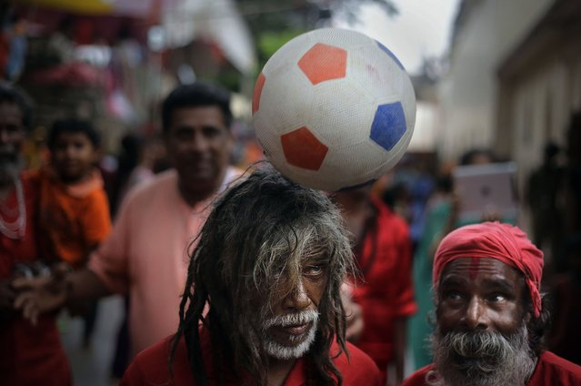 A Sadhu, or Hindu holy man, balances a ball on his head as others watch at the Kamakhya temple in Gauhati, India, Saturday, June 21, 2014. The annual Ambubasi festival begins Sunday where hundreds of tantric Sadhus, holy men from an esoteric form of Hinduism, gather to perform rituals at the temple. (Photo by Anupam Nath/AP Photo)