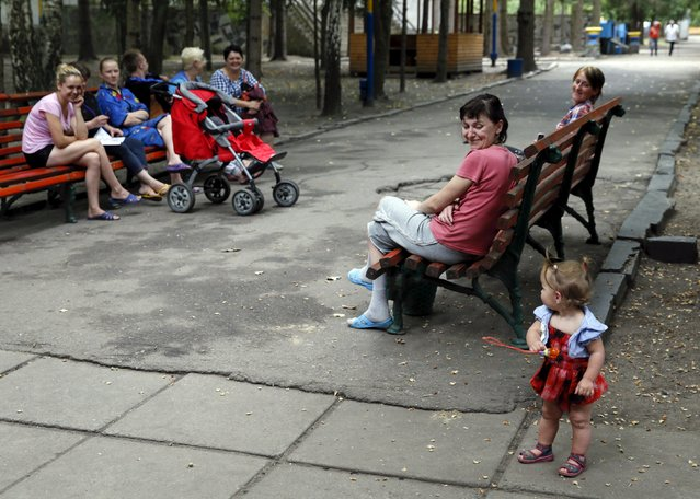 Adults look at a girl as they sit on benches in the compound of a health and rest centre which serves as a temporary accommodation for refugees from eastern regions of the country in the town of Korostyshiv, Zhytomyr region, Ukraine, July 30, 2015. (Photo by Valentyn Ogirenko/Reuters)