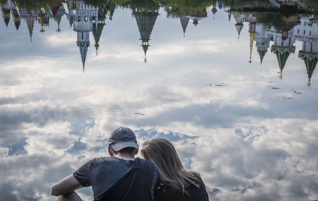 A couple enjoys the view of the ethnographic and amusement center Kremlin in Izmailovo reflected in the Serebryano-Vinogradnii lake in Moscow on July 30, 2017. (Photo by Mladen Antonov/AFP Photo)