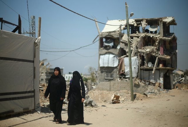 Palestinian women walk in front of a house that witnesses said was destroyed by Israeli shelling during a 50-day war last summer, in the east of Gaza City May 6, 2015. (Photo by Mohammed Salem/Reuters)