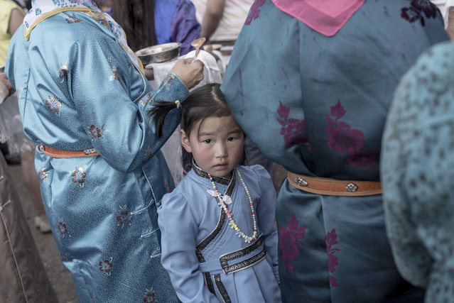 A girl wearing a traditional Mongolian costume waits with her mother during the speech of Mongolian presidential election candidate Battulga Khaltmaa from the Mongolian Democracy Party during a rally  in Ulan Bator, on June 23, 2017. On June 26, Mongolians will elect a president from among three candidates: Enkhbold Miyegombo, leader of the governing Mongolian People's Party (MPP), Battulga Khaltmaa, from the main opposition Democratic Party (DP), and Ganbaatar Sainkhuu, from the Mongolian People's Revolutionary Party (MPRP). (Photo by Fred Dufour/AFP Photo)