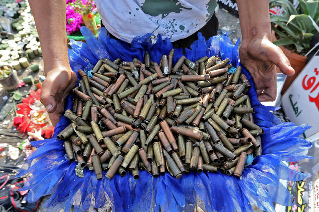 An Iraqi anti-government demonstrator shows a basket full of empty bullet cartridges found in the Iraqi capital's Tahrir Square on December 11, 2019. Since October 1, Iraq's capital and its Shiite-majority south have been gripped by rallies against corruption, poor public services, a lack of jobs and Iran's perceived political interference. (Photo by Sabah Arar/AFP Photo)