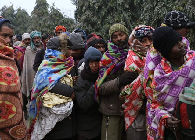 Homeless men stand in a line on the side of a street to collect food on a cold winter morning in the old quarters of Delhi, India, December 29, 2019. (Photo by Anushree Fadnavis/Reuters)