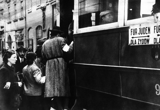 "A scene from the Warsaw Ghetto where Jews are seen wearing white armlets bearing the Star of David and trams are seen marked with the words ""For Jews Only"", on February 17, 1941"