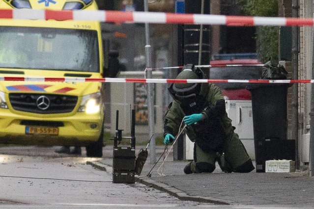 A member of the Explosive Ordnance Disposal team, EOD, examines a suspect package after it was found on the doorstep of Kosher restaurant HaCarmel in Amsterdam, Netherlands, Wednesday, January 15, 2020. (Photo by Peter Dejong/AP Photo)