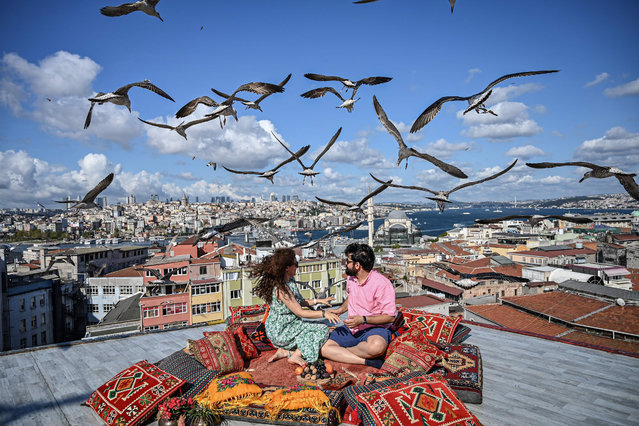 A couple sit on the terrase of a cafe in Istanbul as seagulls fly over them on September 10, 2019. (Photo by Ozan Kose/AFP Photo)