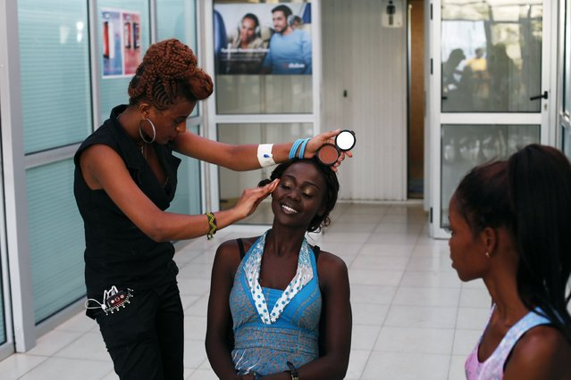 """A contestant has makeup applied before the """"Beauties of South Sudan"""" beauty contest in Juba, South Sudan, on Jule 13, 2014. (Photo by Andreea Campeanu/Reuters)"""