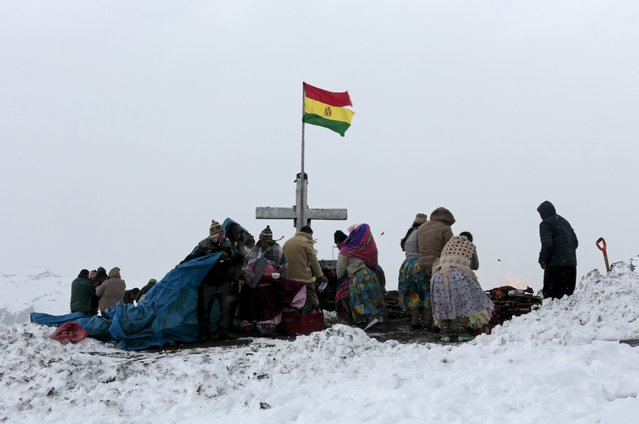 Aymara people gather for an offering during a snow storm in La Cumbre, near La Paz, BOLIVIA August 12, 2015. (Photo by David Mercado/Reuters)