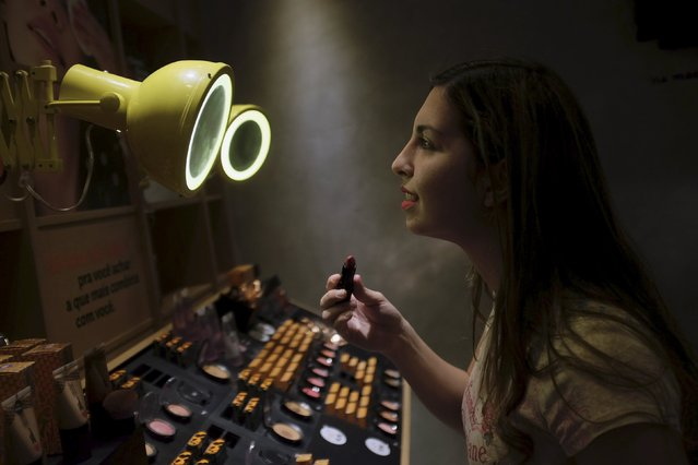 A woman checks lipstick applied on her lip, inside of a cosmetics shop in Sao Paulo, Brazil August 13, 2015. From cigarettes to lipstick to sandals, exports have emerged as a silver lining for Brazilian consumer goods companies that are suffering the worst domestic slump in over a decade. (Photo by Nacho Doce/Reuters)