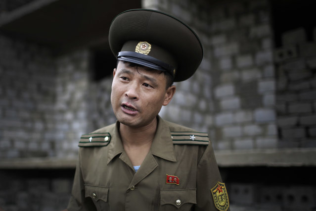 In this Friday, July 21, 2017, photo, Maj. Jong Il Hyon, 44, a member of a bomb squad for South Hamgyong, speaks to The Associated Press at a construction site on the outskirts of Hamhung, North Korea's second-largest city, where workers unearthed a rusted but still potentially deadly mortar round in February. Over the years, Maj. Jong Il Hyon, a 10-year veteran, has lost five colleagues to explosions. He carries a lighter one gave him before he died. He also bears a scar on his left cheek from a bomb disposal mission gone wrong. (Photo by Wong Maye-E/AP Photo)