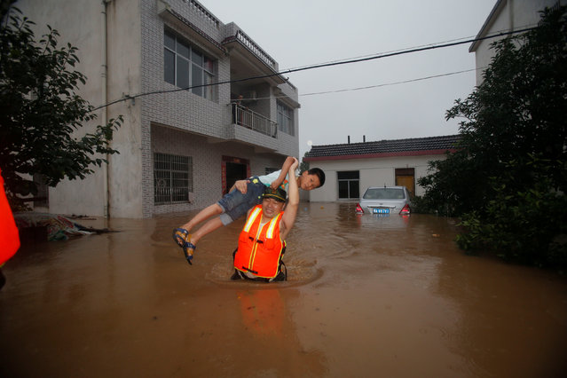 A rescuer saves a resident from a flooded area in Wuhan, Hubei Province, China, July 2, 2016. (Photo by Reuters/China Daily)