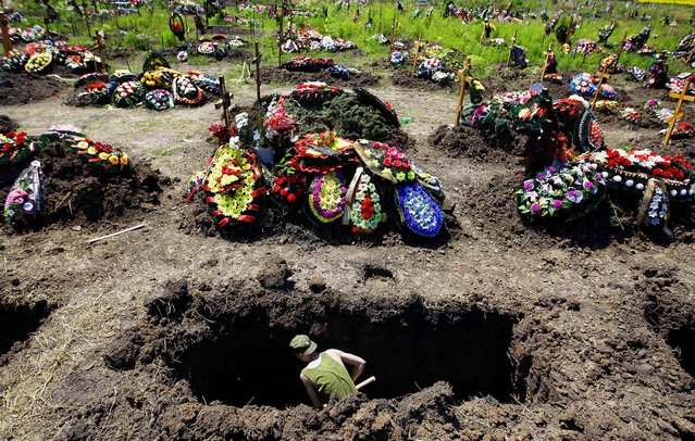 A soldier digs a grave for those who died during floods in Krymsk, Russia on July 10, 2012