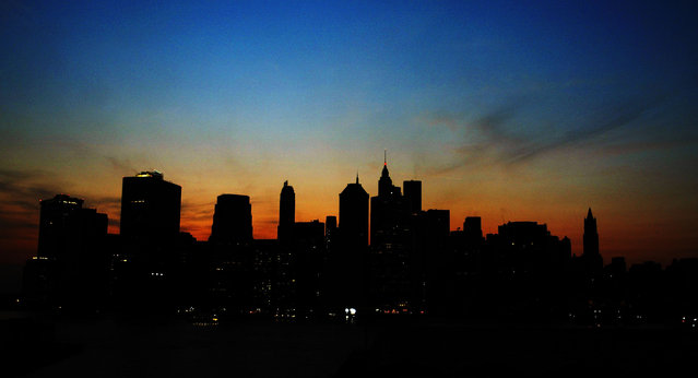 Sun sets over the Manhattan skyline August 14, 2003 during a major power outtage affecting a large part of the north eastern United States and Canada. (Photo by Robert Giroux/Getty Images)