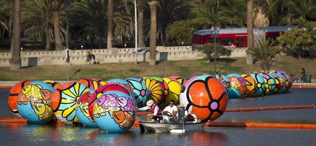 "Volunteers lower an inflated sphere into MacArthur Park Lake during the installation of Portraits of Hope's exhibition ""Spheres at MacArthur Park"" in Los Angeles, California August 21, 2015. (Photo by Mario Anzuoni/Reuters)"