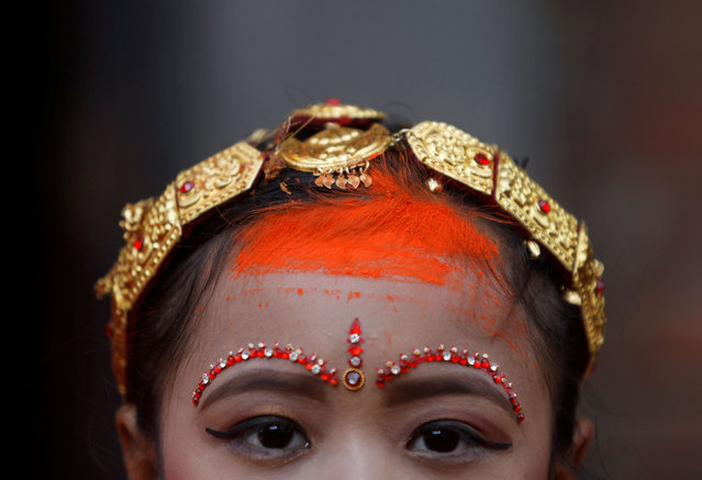"A girl from Newar community is pictured with vermillion powder on her forehead as she takes part at the Ihi ceremony in Bhaktapur, Nepal on December 6, 2019. The two-day ceremony begins with purification rituals and ends with ""Kanyadan"" (giving away the virgin) of the girl by her father. A Newari girl gets married thrice in her life, first with Bel, the fruit of a wood-apple tree, secondly with the sun, and lastly with her future husband. (Photo by Monika Deupala/Reuters)"