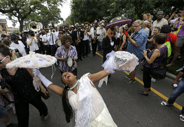People participate in a jazz funeral for Lionel Ferbos, who was one of New Orleans' oldest traditional jazz musicians, in New Orleans, Saturday, August 2, 2014. The city said good-bye to Ferbos with a Mass presided over by Archbishop Gregory Aymond and a traditional second-line parade. The 103-year-old Ferbos died July 19. (Photo by Gerald Herbert/AP Photo)