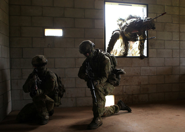 Australian Army soldiers with the 2RAR breach a building during a helicopter insertion exercise with US Marines in the Kahuku mountains training area during the multi-national military exercise RIMPAC in Honolulu, Hawaii, July 13, 2016. (Photo by Hugh Gentry/Reuters)