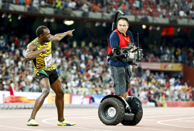 Usain Bolt of Jamaica poses as a cameraman on a segway rides past after winning the men's 100m final during the 15th IAAF World Championships at the National Stadium in Beijing, China in this August 23, 2015 file photo. Bolt collided with the same cameraman after winning the men's 200m final on August 27, 2015. (Photo by Lucy Nicholson/Reuters)