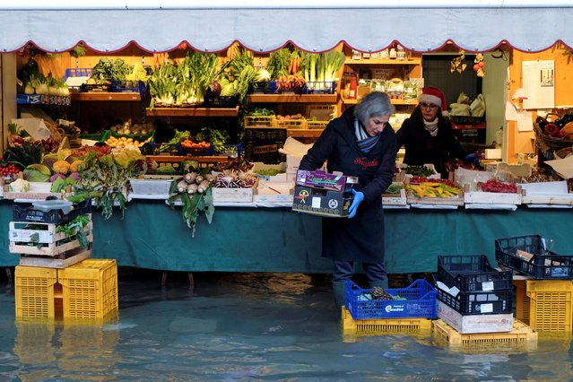 A woman carries a box in front of her vegetable stand during high tide in Venice, Italy on December 24, 2019. (Photo by Manuel Silvestri/Reuters)