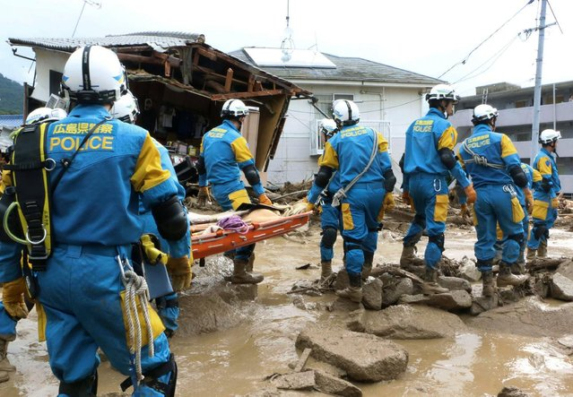 A troop of police rescue personnel head out for rescue operation after a massive landslides swept through residential area in Hiroshima, western Japan, Wednesday, August 20, 2014. (Photo by Shinpei Hamaguchi/AP Photo/Kyodo News)