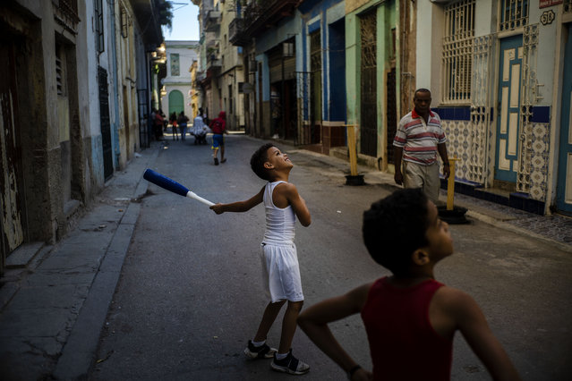 A boy smiles while playing baseball on the street with a friend in Havana, Cuba, Wednesday, March. 11, 2020. (Photo by Ramon Espinosa/AP Photo)