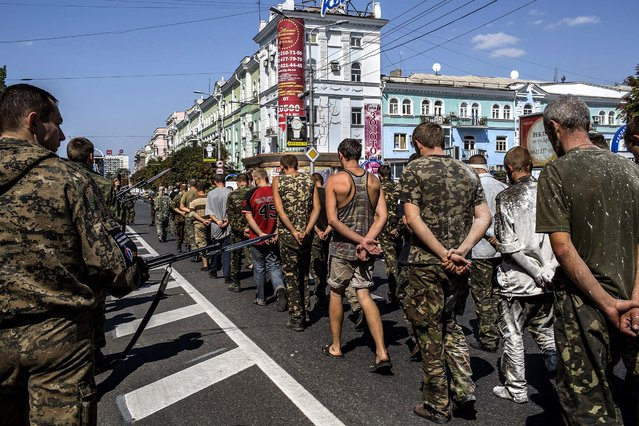 Armed pro-Russian separatists force Ukrainian prisoners of war to parade through the streets of Donetsk, on August 24, 2014. Sunday, Ukraine's national day of independence, was celebrated in a different fashion in Kiev, where onlookers cheered troops and armored vehicles in a display of martial fervor. (Photo by Mauricio Lima/The New York Times)