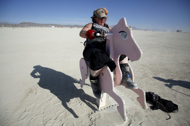 """Kentucky Sunshine, her Playa name, rides a rocking horse art installation during the Burning Man 2015 """"Carnival of Mirrors"""" arts and music festival in the Black Rock Desert of Nevada, August 31, 2015. (Photo by Jim Urquhart/Reuters)"""